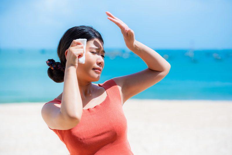 太陽の強い日差しから手で顔を覆う女性のイメージ