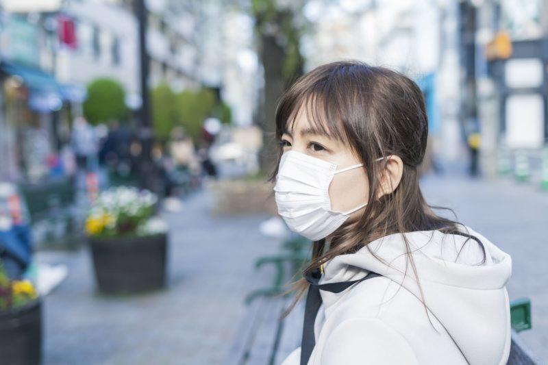街中でマスクをしている冬服の女性