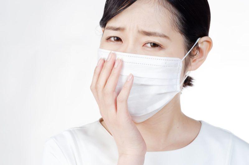 マスクを着けて不調を訴えている女性の顔