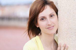 コンクリート柱から顔を出している外国人美女