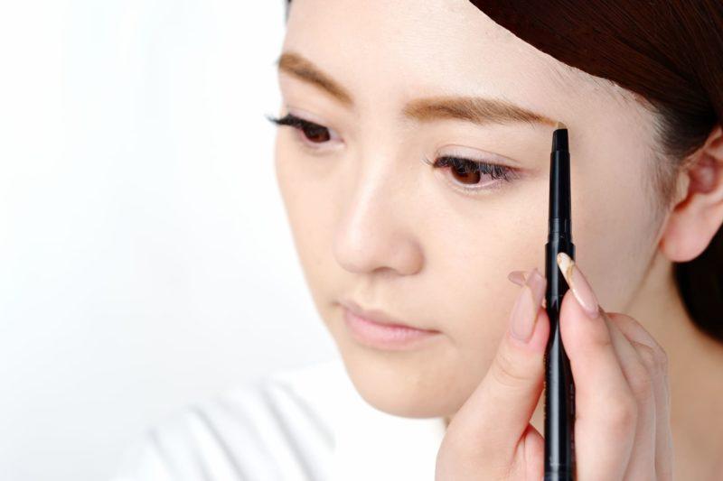 斜め下の鏡に向かってペンシルで眉毛を整えている女性
