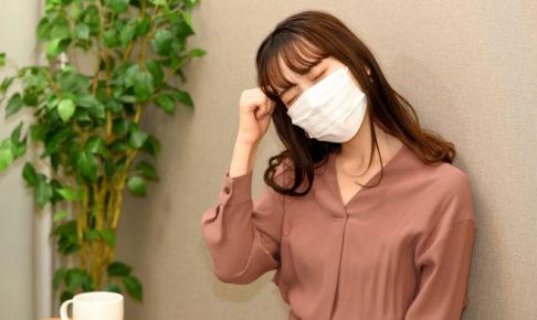 オフィスでマスクをして苦しそうにしている女性