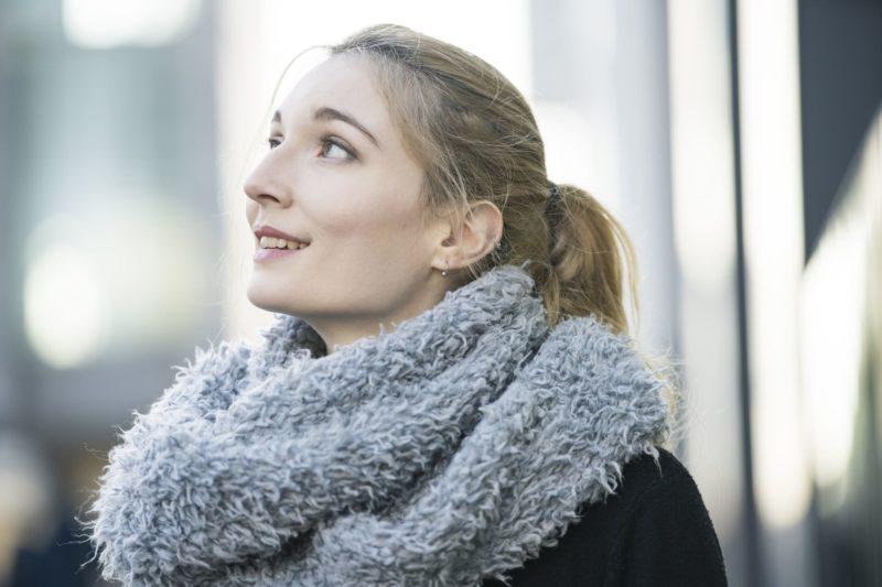 冬の街をスヌードをつけて過ごしている外国人女性