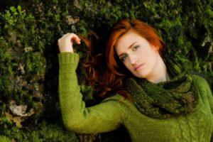 コケの上に寝そべっているグリーンニットの美女