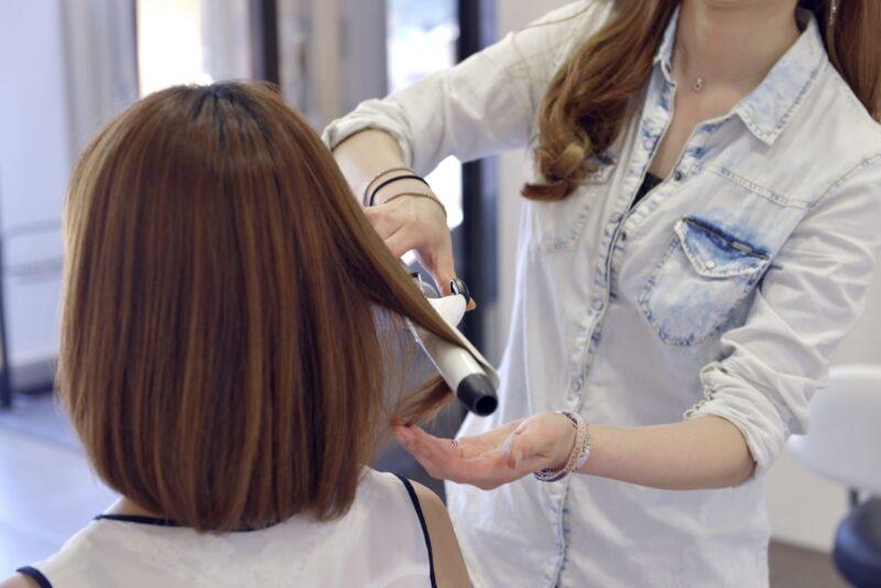美容院でヘアアイロンをやってもらっている光景