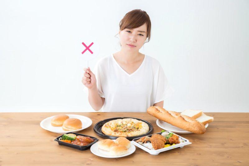 油物や炭水化物の食べ物を前にダメサインを出している女性