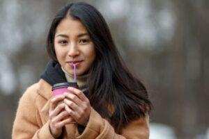 冬にテイクアウトのコーヒーを飲んでいる黒髪女性