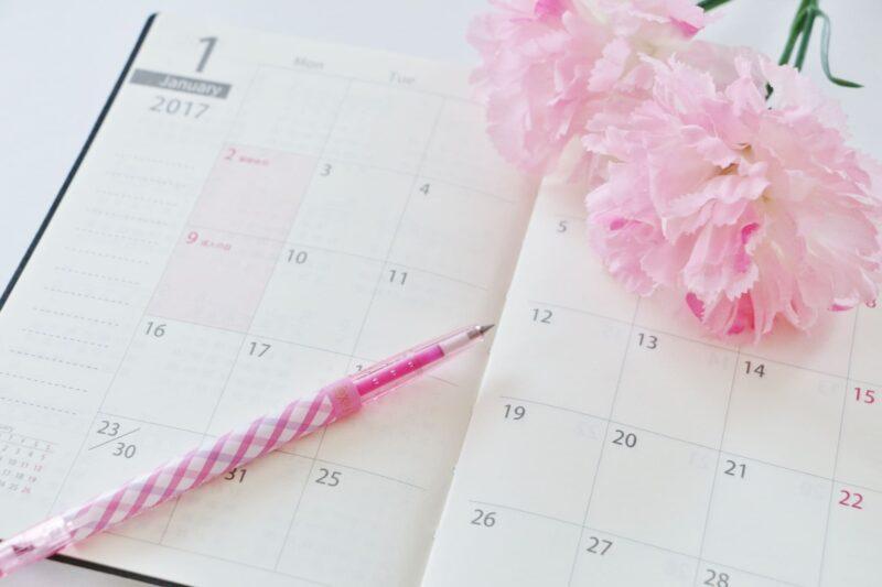 ピンクのカーネーションとペンが添えられている手帳
