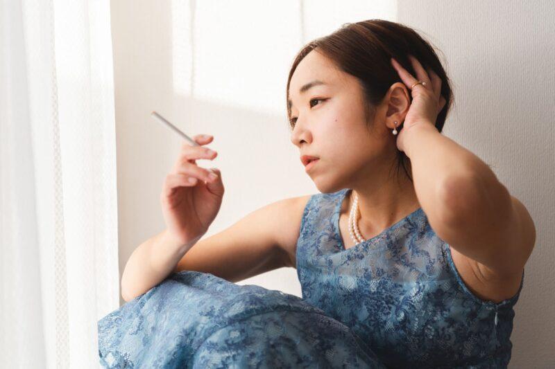 窓辺でタバコをくゆらせている青ドレスの女性
