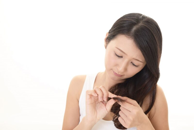 自分のロングヘアの髪が気になる女性