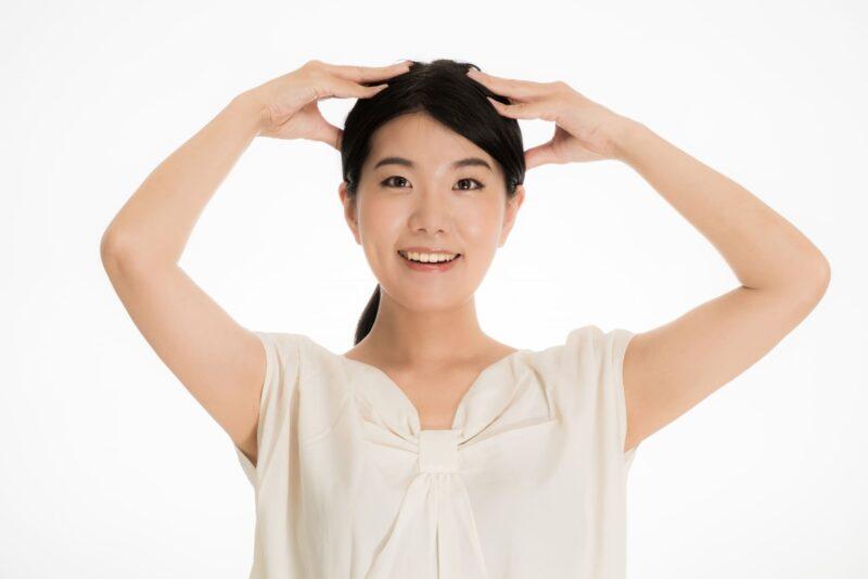 自分の頭皮を晴れやかな顔でマッサージしている女性