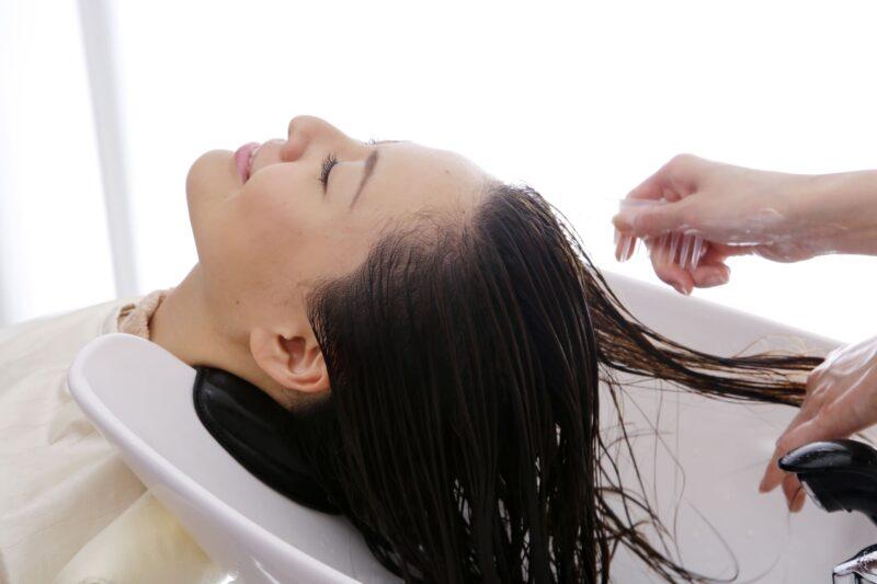 美容室でシャンプーをやってもらっている女性