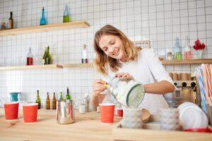 カフェでコーヒーに砂糖を入れようとしている外国人女性スタッフ