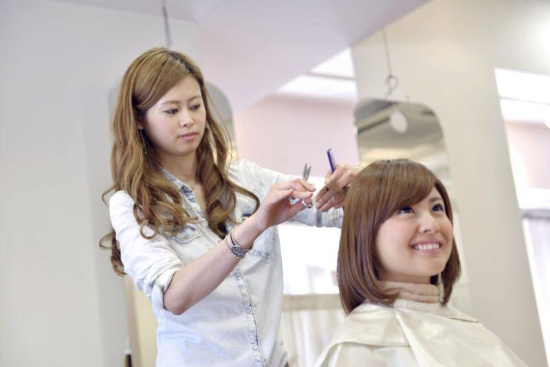 おしゃれな美容師さんの下でヘアカットをしてもらう女性