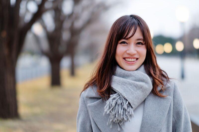 冬の日にグレーのコーデで微笑むロングヘアの女性