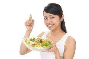 サラダを抱える笑顔の女性