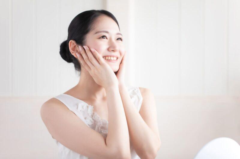 朝日を浴びながらスキンケアをしている白いノースリーブ女性