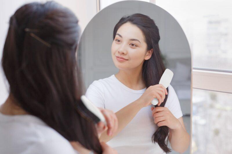 鏡を見ながら髪をとかしてケアをしている女性