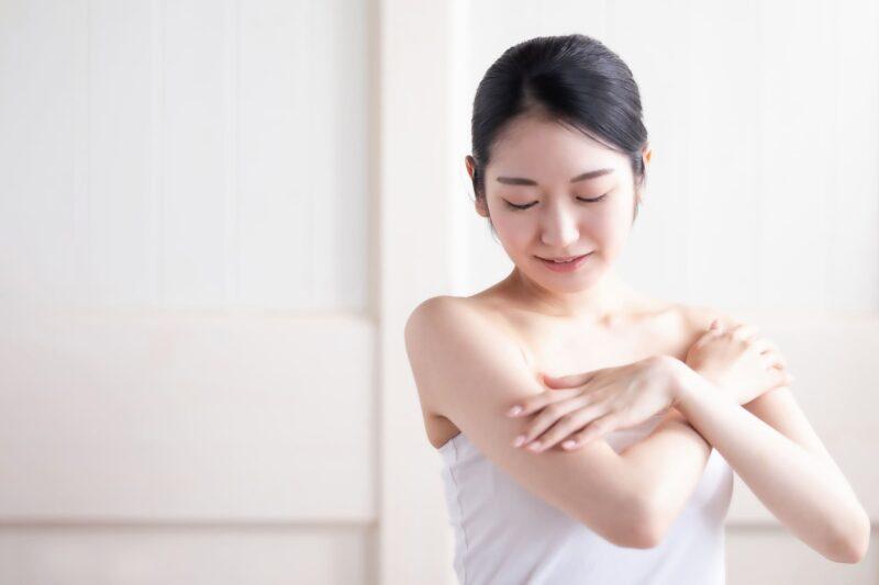 腕を撫でるタオルの女性