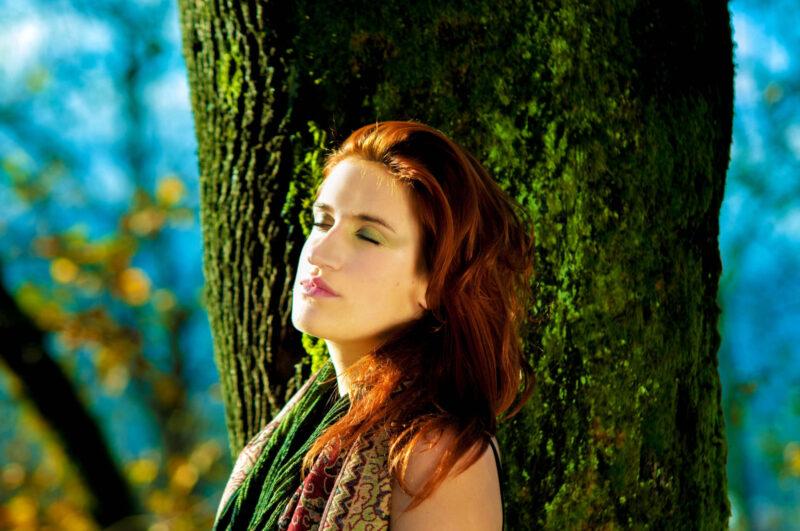 森の中で木と同化しながら目をつむっている女性