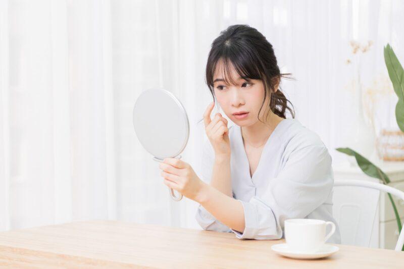 ダイニングテーブルで鏡を見ながら自分の肌に疑問を持っている女性