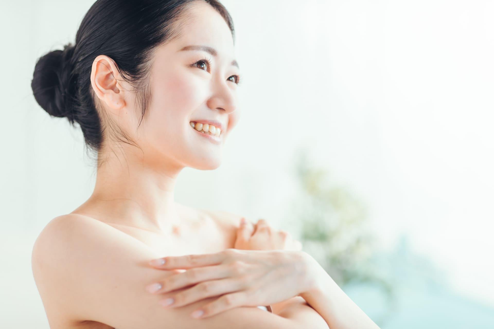 晴れやかな顔でローションを体に塗っている女性