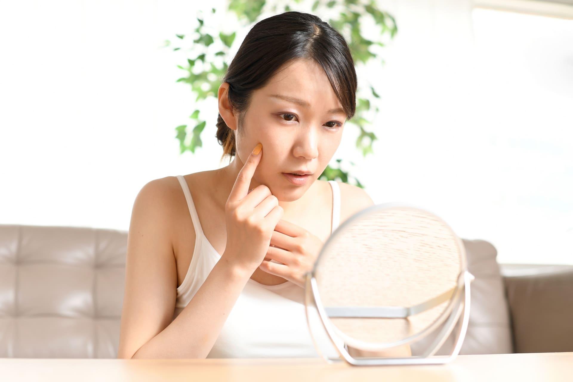朝に鏡を見て自分の肌の状態にショックを受けている女性